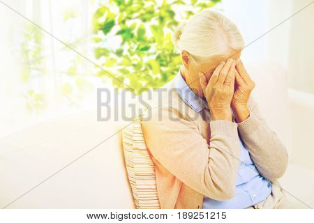 stress, age and people concept - senior woman suffering from headache or grief over window with green natural background