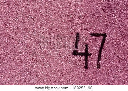 Number Fourty Seven On Pink Plaster Wall.