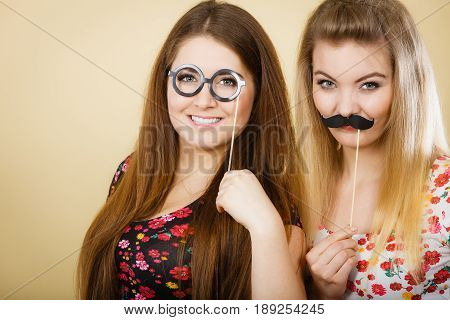 Two Women Holding Moustache And Eyeglasses On Stick