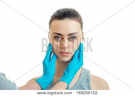 horizontal portrait of a young girl on the serious doctor with blue mittens isolated on white background