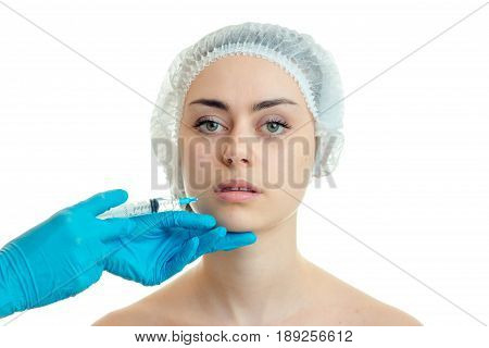 surgeon makes an analgesic injection in the face of a young girl isolated on a white background close-up