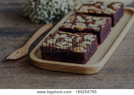 Homemade dark chocolate brownies topping with almonds slices. Fudge brownies on wood plate on rustic wood table. Fudge brownies is one type of chocolate cake. Square shape of chocolate brownies in vintage tone for background or wallpaper.