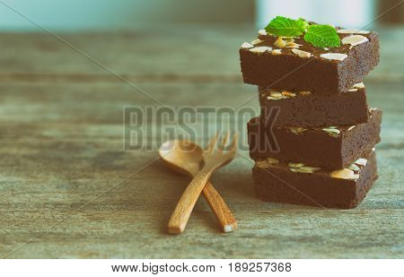 Piece of stack homemade dark chocolate brownies topping with almonds slices and mint on wood table.Bittersweet and fudge.Brownie is one type of chocolate cake. Vintage tone.