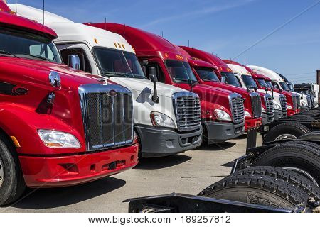 Indianapolis - Circa June 2017: Colorful Semi Tractor Trailer Trucks Lined up for Sale XV