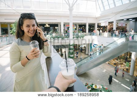 Young woman talking on the phone while walking mall with smoothie, firts-pesron view