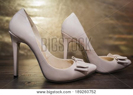 Women's beige lacquered shoes with a pointed nose and a bow on a high thin heel on a golden and dark wooden background