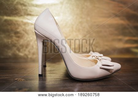 Women's beige lacquered shoes with a pointed nose and a bow on high heels on a dark wooden and gold background