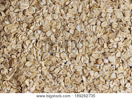 Top view or oat flakes or oatmeal for background and texture. Rolled oat is clean food for health. Prepare oat flakes for cooking or bakery. Old-fashioned oat flakes background for web design. Natural style of oatmeal background concept.