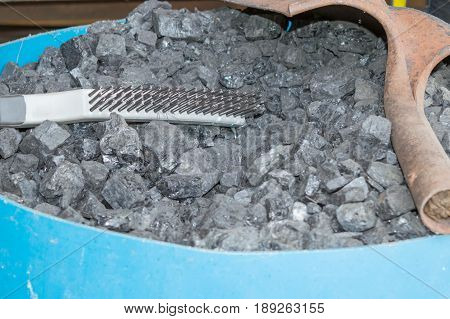 A wire brush and old shovel sit on top of a barrel of blacksmithing coal