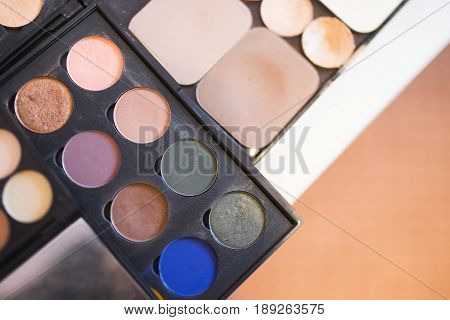A palette of shades of beige brown green and blue shades and light beige powder for professional make-up.