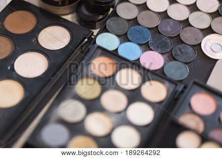 A pallet of beige concealers and shades of blue shades for professional make-up on a black background