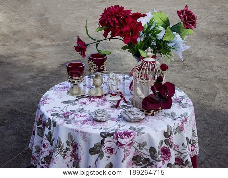Table With Ceramic Angels And Red Roses