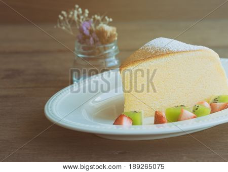Homemade Japanese cheesecake. Delicious soft cheesecake fluffy,lite and soft.  Japanese cotton cheesecake sparkling icing fresh fruit: kiwi and strawberry. Japanese cheesecake on white plate. Cotton Japanese cheesecake on rustic wood table.