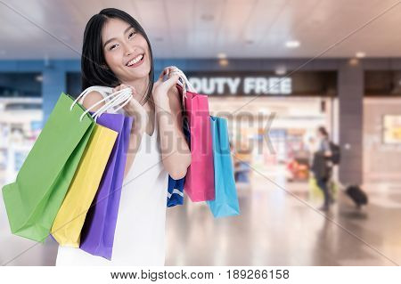 Beautiful Asian woman with shopping bags in duty free in International Airport before departure. Sale shopping tourism and happy people concept