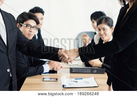 Asian business man and business woman shaking hands in conference room. Business people shaking hands agreement concept.