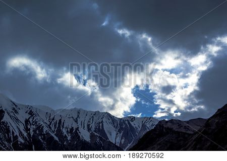 Mountain landscape, beautiful view of the picturesque gorge, high snow slopes, the cloudy sky over mountains, the nature of the Caucasus, Georgia