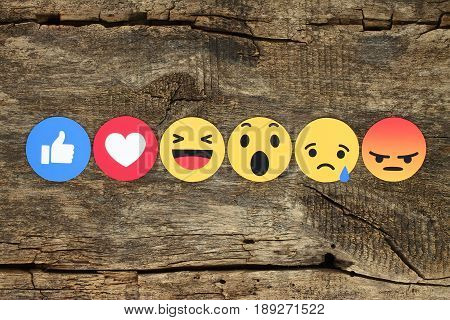 Kiev Ukraine - February 07 2017: Facebook like button 6 Empathetic Emoji Reactions printed on paper and placed on wooden background. Facebook is a well-known social networking service