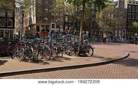 Amsterdam, Netherlands - May 13, 2017: Much Bicycles Parking And Traditional Old Dutch Houses Near T