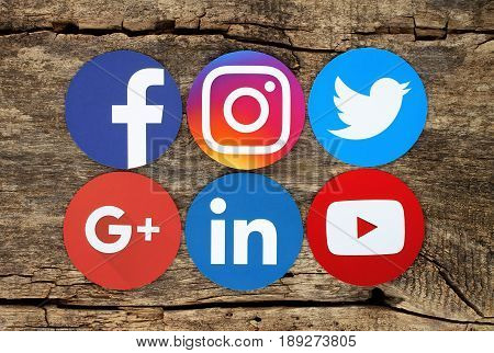 Kiev Ukraine - March 03 2017: Famous round social media icons such as: Facebook Twitter Instagram Linkedin Google Plus and Youtube printed on paper and placed on wooden background
