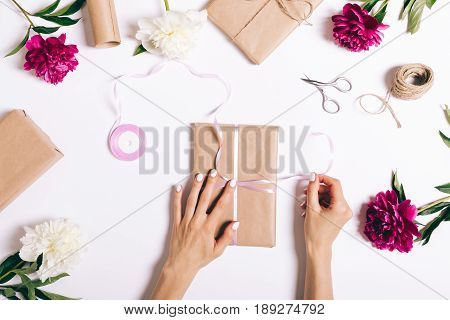 Female Hands Tie A Ribbon On A Gift For A Holiday On A White Table