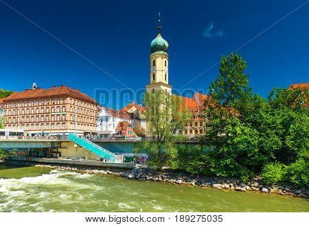 Graz - May 2017, Austria: The old city center on sunny day. Franciscan Church, old historical buildings with orange roofs against the blue sky and the flowing river Mur