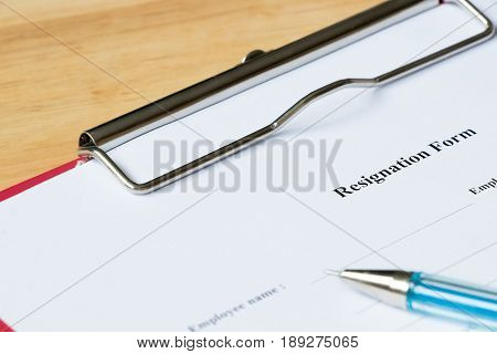 Job resignation form with pen on wood desk background