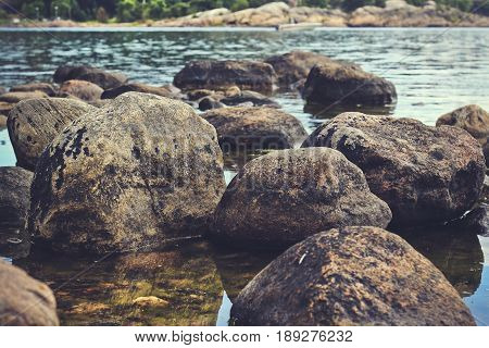 Boulders on the shoreline with the seawater in the background.