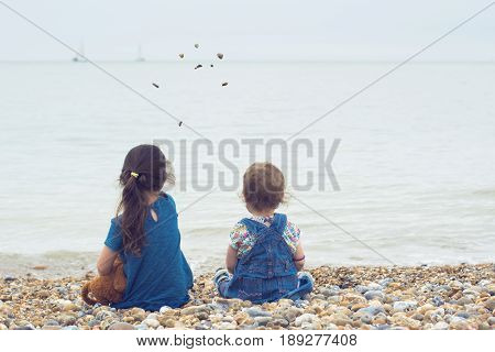 Tow Little Girls Sitting On The Beach