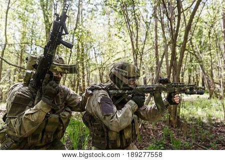 Two officers with assault rifles in woods during day