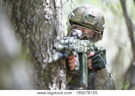 Sniper with rifle peeks out from behind tree in forest