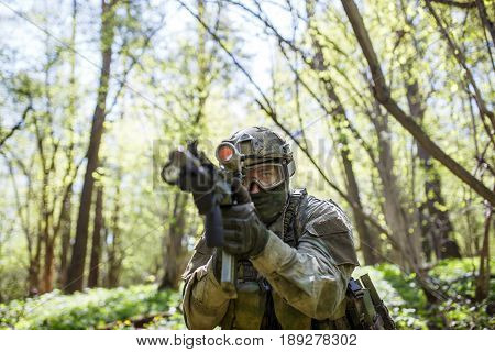 Military man aiming holding submachine gun in forest on mission