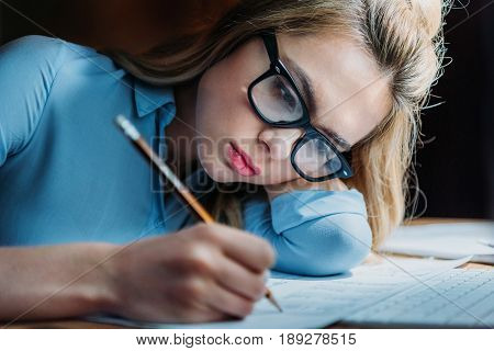 Tired Blonde Caucasian Student In Eyeglasses Lying On Hand And Writing Something With Pencil, Studyi