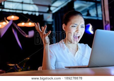 Emotional Asian Businesswoman Yelling While Looking At Laptop With Gesture