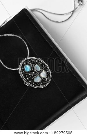 Vintage silver medallion with turquoise and nacre in jewel box closeup