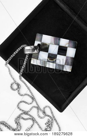Black and white chess nacre pendant in jewel box closeup