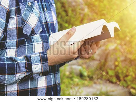 Man reading a book in the park. Student studying memorizing notes outdoors. Young man wearing shirt and reading book. Photo stock.