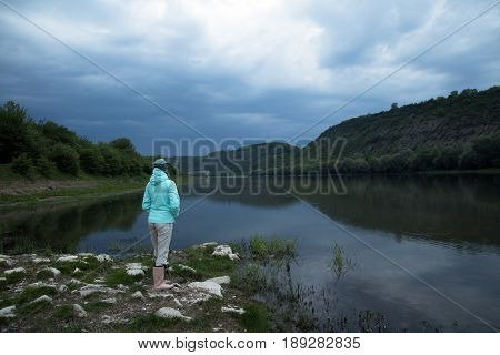 female stands near the river and looks into the distance. Blue storm clouds at twilight