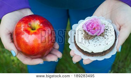 Fat woman wants to lose weight diet top view in blue suit on green grass selects red big apple or round brown with white cake with rose of pink color holds them in hands with short blue nails on blurred background