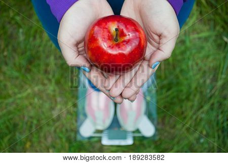 Fat woman wants to lose weight diet top view in a blue suit is standing on transparent glass scales in pink sneakers on green grass holding a large red apple with short blue nails on a blurred background