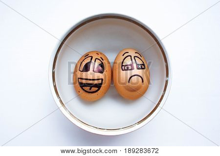 Egg with a cheerful painted face. Photo for your design. To swim in a plate: a pissimist and an optimist. Boiled, boiled eggs.