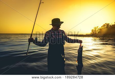 A Fisherman With A Fishing Rod In His Hand And A Fish Caught Stands In The Water Against A Beautiful