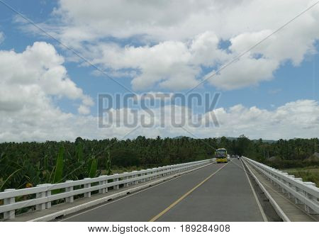 Long bridge ahead Vehicles travel through a long bridge above a river and banana plantations in Tagum, Davao del Norte, Philippines.