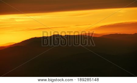 Sunrise above the mountaintops The sun rises above the mountaintops casting a golden orange glow in the skies