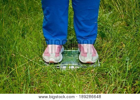 Sport sportswoman fat woman lose weight standing on the scales legs, blue sports trousers knee-deep in pink sneakers glass transparent scales on green grass blurred background front view