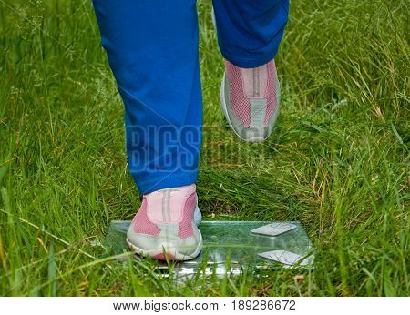 Sport sportswoman fat woman lose weight is standing on the scales legs right leg raised blue sports trousers knee-deep in pink sneakers glass transparent scales on green grass blurred background front view