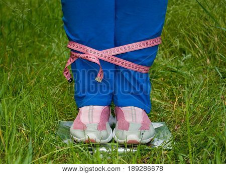 Sport sportswoman fat woman lose weight is standing on the scales legs connected pink measuring tape, figures, blue sports trousers knee-deep in pink sneakers glass transparent scales on green grass blurred background front view