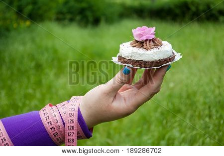 Lose weight fat woman close-up of the right hand holding a cake white with brown with a pink rose white napkin short nails blue on a background of green grass blurred background pink measuring tape wound on the hand side view