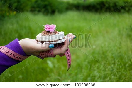 Lose weight fat woman close-up of the right hand bent holding a cake white with brown with a pink rose white napkin short nails blue on a background of green grass blurred background pink measuring tape wound on the hand side view