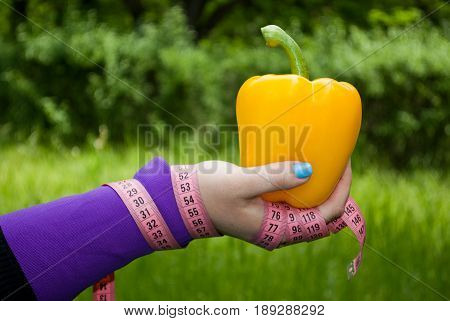 Lose weight fat woman close-up of the right hand holds a big yellow concussion bell pepper short nails blue on a background of green grass blurred background pink measuring tape wound on the hand side view