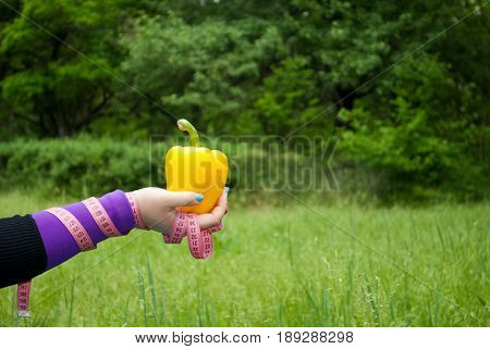 Lose weight fat woman close-up in the distance right hand holds a big yellow sweet bell pepper short nails blue on a background of green grass blurred background pink measuring tape wound on the hand side view